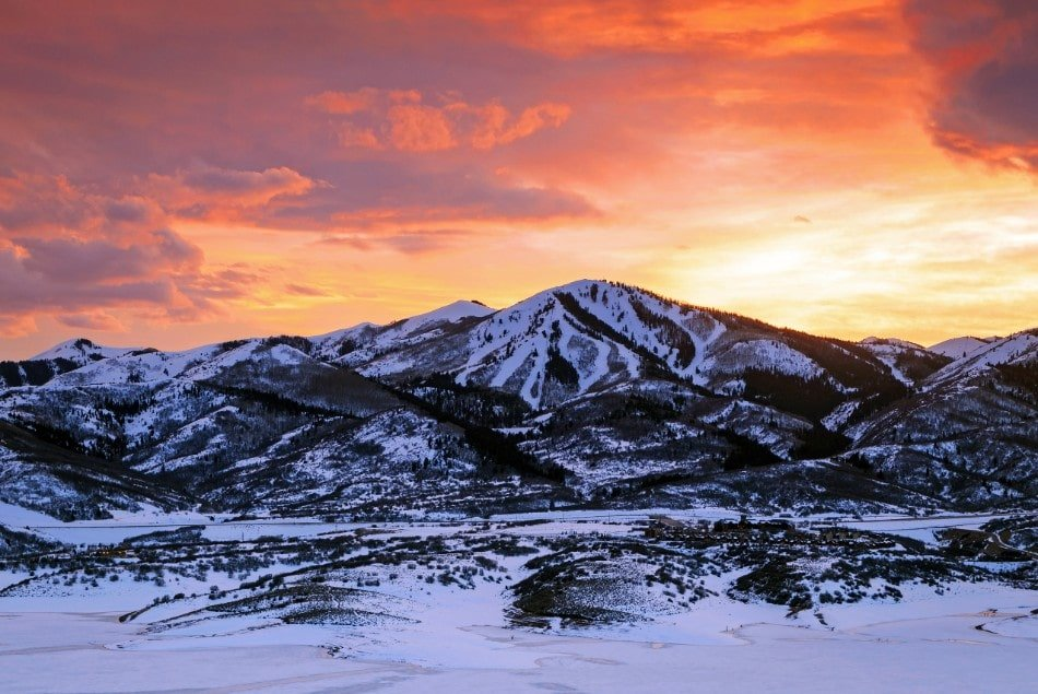 Mountain near Park City Utah covered in snow with orange sky